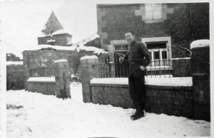 Flynn in front of the house where he and other soldiers stayed in Belgium, February 1945.