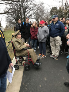 John A. Pildner, Sr. addresses a group of visitors at the memorial marker for the Veterans of the Battle of the Bulge.