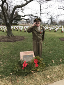 John A. Pildner, Sr. saluting at the memorial marker for the Veterans of the Battle of the Bulge at Arlington National Cemetery.